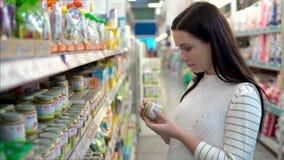 La giovane donna sceglie gli alimenti per bambini nel supermercato, madre sceglie l'alimento per il loro bambino nel mercato, sup video d archivio