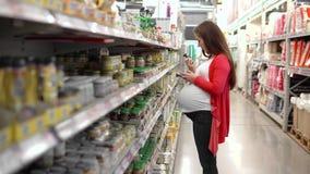 La giovane donna sceglie gli alimenti per bambini nel supermercato, madre sceglie l'alimento per il loro bambino nel mercato, sup archivi video