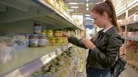 La giovane donna sceglie gli alimenti per bambini nel supermercato, madre sceglie l'alimento per il loro bambino nel mercato, sup stock footage