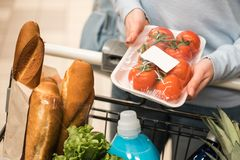 La giovane donna sceglie i pomodori freschi al supermercato fotografia stock