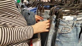 La giovane donna sceglie i vestiti video d archivio