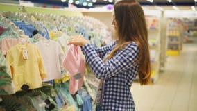 La giovane donna sceglie i vestiti per un bambino stock footage