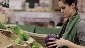 La giovane donna sceglie il cavolo sugli scaffali di negozio video d archivio