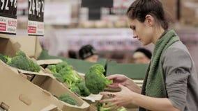 La giovane donna sceglie il cavolo sugli scaffali di negozio stock footage