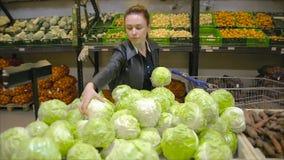 La giovane donna sceglie il cavolo sul supermercato video d archivio