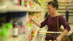 La giovane donna sceglie Juice From lo scaffale del supermercato Ha molti oggetti in suo carretto del supermercato stock footage