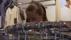 La giovane donna sceglie l'abbigliamento in deposito stock footage