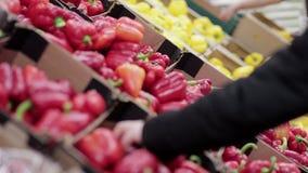 La giovane donna sceglie la paprica sugli scaffali di negozio stock footage