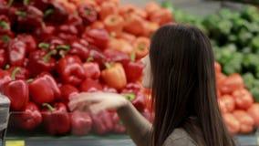 La giovane donna sceglie la paprica sugli scaffali di negozio video d archivio