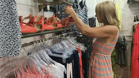 La giovane donna sceglie le scarpe nel negozio video d archivio