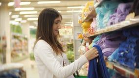 La giovane donna sceglie un asciugamano in un deposito per i prodotti domestici video d archivio