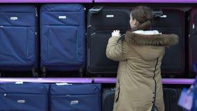 La giovane donna sceglie una valigia nel supermercato stock footage