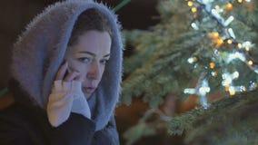 La giovane donna in sciarpa parla sul telefono ai precedenti dell'abete stock footage
