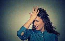 La giovane donna sciocca, schiaffeggiante la mano sulla testa che ha duh momento ha fatto l'errore Fotografia Stock
