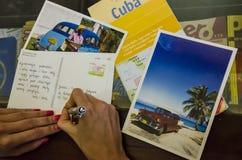 La giovane donna scrive le cartoline d'auguri da Cuba Fotografia Stock Libera da Diritti