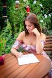 La giovane donna scrive nel giardino dell'estate in un taccuino o in un diario immagine stock libera da diritti