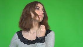 La giovane donna scuote il suo pugno mentre esamina la macchina fotografica sopra fondo verde stock footage