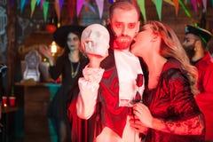 La giovane donna sexy agghindato come un morso del vampiro suo equipaggia il collo agghindato come Dracula per Halloween immagine stock