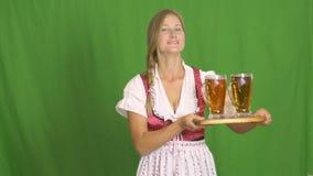 La giovane donna sexy che porta un dirndl con due tazze di birra più sul verde ha isolato il fondo video d archivio