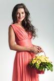 La giovane donna sexy con il canestro del fiore sta ridendo Fotografia Stock