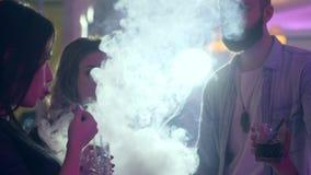 La giovane donna sexy gode del narghilé ed esala il fumo vicino agli amici che tiene i cocktail al partito video d archivio