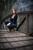 La giovane donna si accovaccia al ponte Fotografie Stock