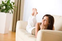La giovane donna si distende la menzogne giù sul sofà immagini stock
