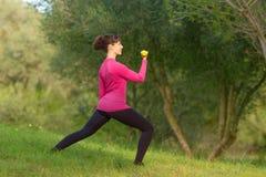 La giovane donna si diverte con peso che si prepara all'aperto nel parco Fotografia Stock Libera da Diritti