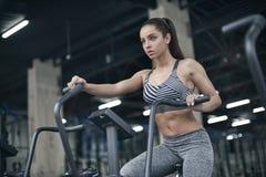 La giovane donna si esercita allenamento di stile di vita sano della palestra nel cardio sulla bici Fotografia Stock