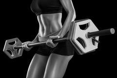 La giovane donna si esercita con il bilanciere isolato sopra backgroun nero Fotografia Stock Libera da Diritti