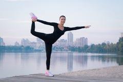 La giovane donna si esercita sul pilastro durante l'allenamento di addestramento di mattina Immagini Stock