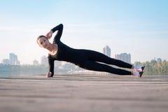La giovane donna si esercita sul pilastro durante l'allenamento di addestramento di sport Immagine Stock