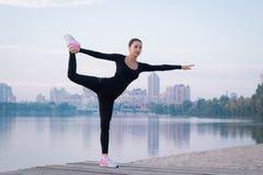La giovane donna si esercita sul pilastro durante l'allenamento di forma fisica di mattina Fotografie Stock