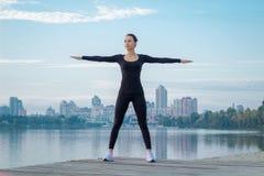 La giovane donna si esercita sul pilastro durante la forma fisica di mattina che prepara il wo Fotografia Stock Libera da Diritti