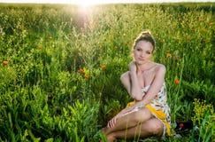 La giovane donna si rilassa nel campo del papavero Fotografia Stock Libera da Diritti
