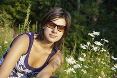 La giovane donna si rilassa sul campo della margherita immagine stock