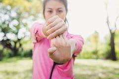La giovane donna si scalda il suo corpo allungando le sue armi per essere pronta per l'esercitazione e per fare l'yoga nel parco Immagini Stock