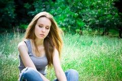 La giovane donna si siede immagine stock libera da diritti