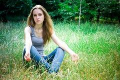 La giovane donna si siede ed esamina la macchina fotografica fotografia stock
