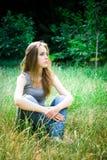 La giovane donna si siede, a gambe accavallate fotografia stock libera da diritti