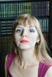 La giovane donna si siede nella sala con gli scaffali per libri Fotografie Stock