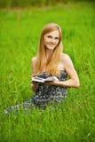 La giovane donna si siede su erba Fotografia Stock