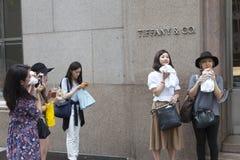 La giovane donna si siede su pavimentazione vicino al ground zero e scrive sulla parete Fotografia Stock