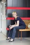 La giovane donna si siede su un banco Immagini Stock