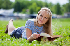 La giovane donna si siede su un'erba in sosta. Fotografia Stock Libera da Diritti
