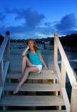 La giovane donna si siede sui punti alla discesa al mare alla notte maldives Immagini Stock