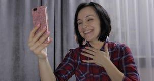 La giovane donna si siede sul letto e sul godere avendo video chiacchierata facendo uso dello smartphone fotografie stock