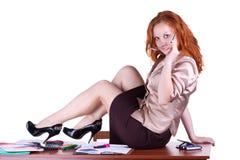 La giovane donna si siede sulla tabella Fotografie Stock Libere da Diritti