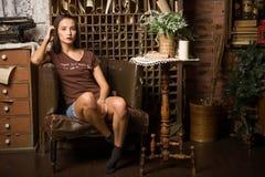 La giovane donna si siede in una poltrona Fotografie Stock Libere da Diritti