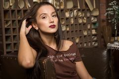 La giovane donna si siede in una poltrona Fotografia Stock Libera da Diritti